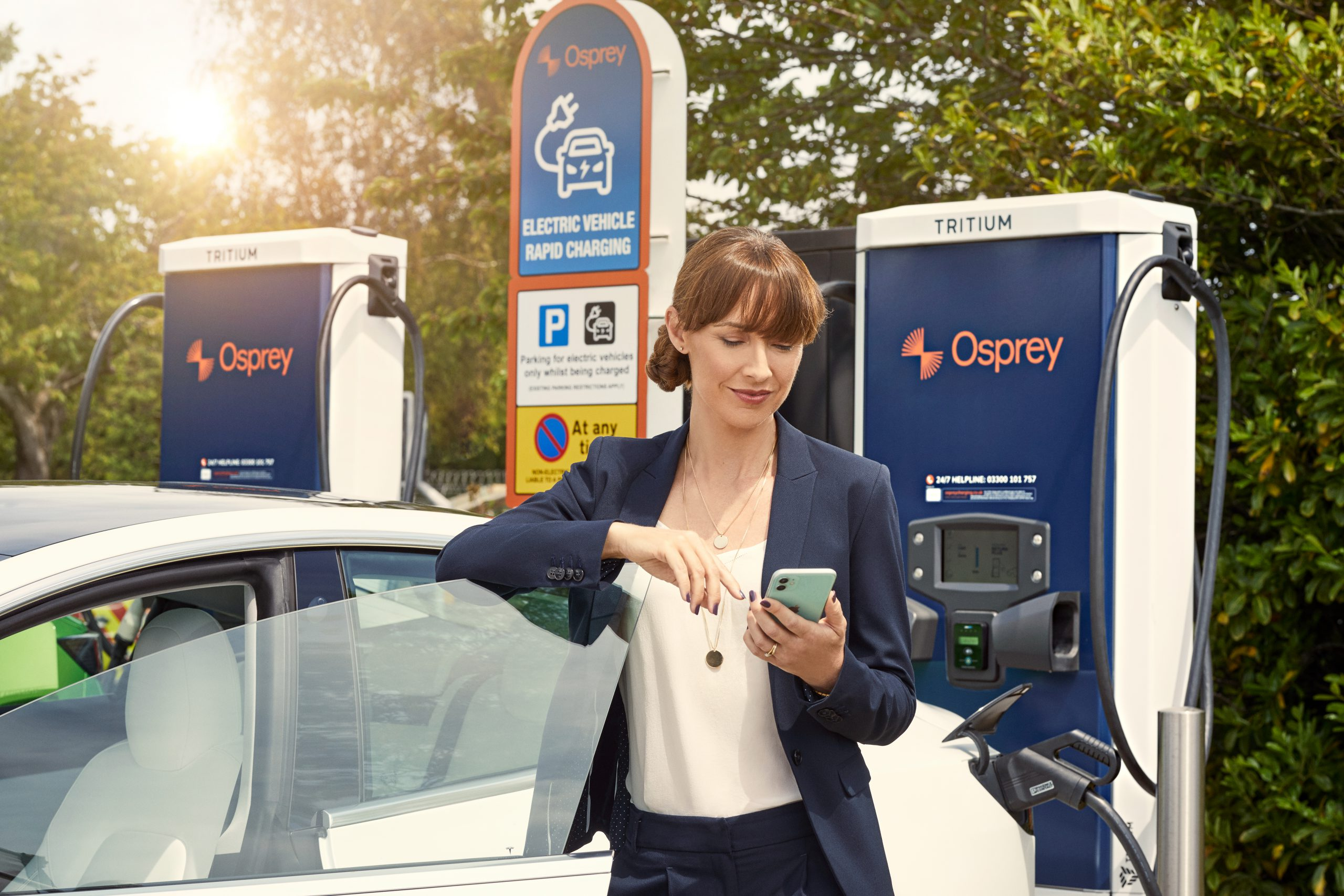 Woman charging car on Osprey charger Paua electric fuel card